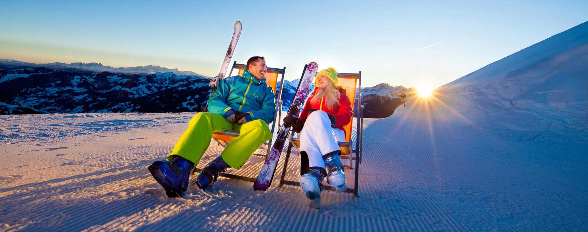 Easter skiing - Niche Destinations 4-star-superior hotel GROSSARLER HOF couple skiing at sunset