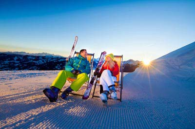 Easter skiing - Niche Destinations 4-star-superior hotel GROSSARLER HOF couple skiing at sunset
